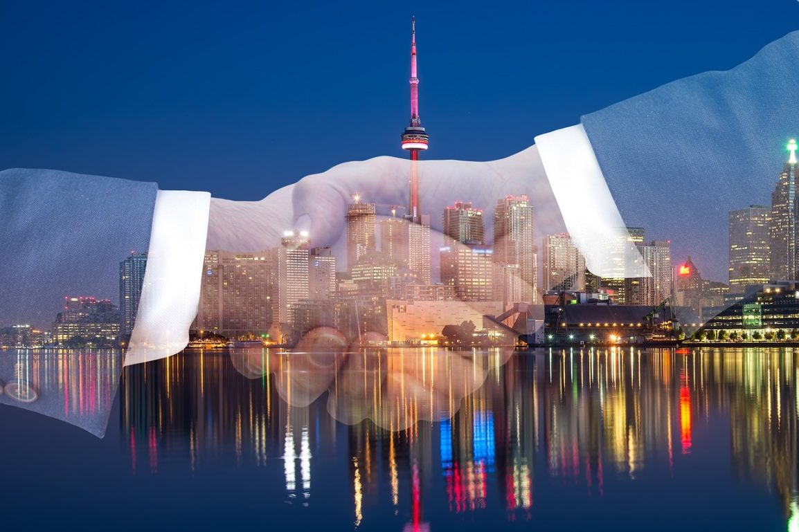 2 hands shaking superimposed over a city scene at night