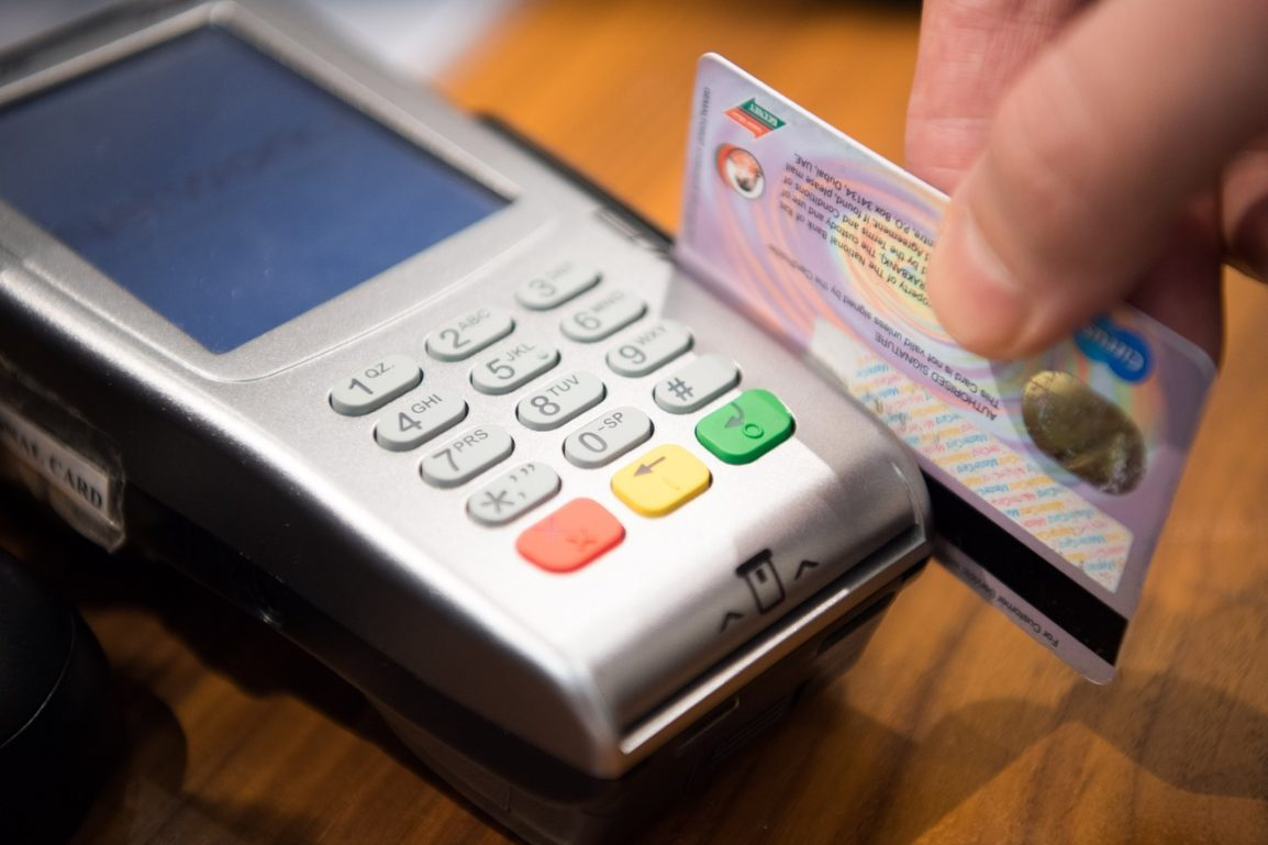 fingers holding a credit card and scanning in a card reader
