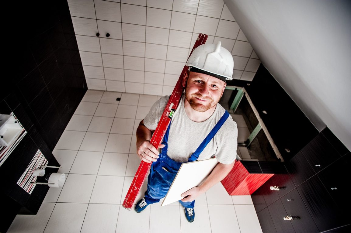 Construction worker wearing hard hat holding tools in an office and smiling at the camera