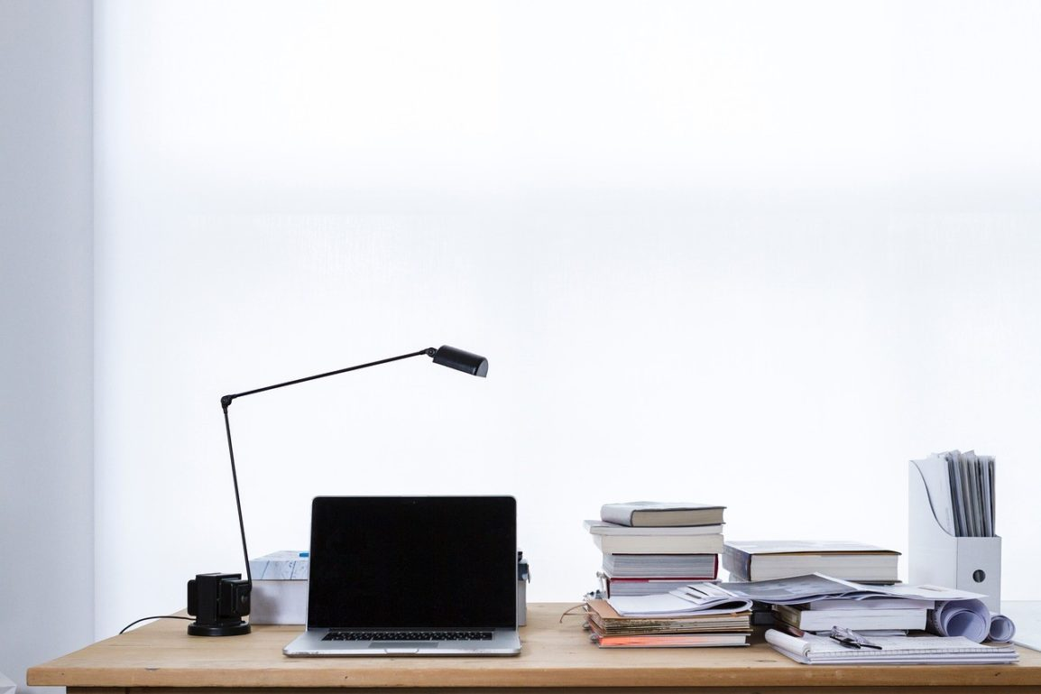 Desk with books, laptop and desk lamp