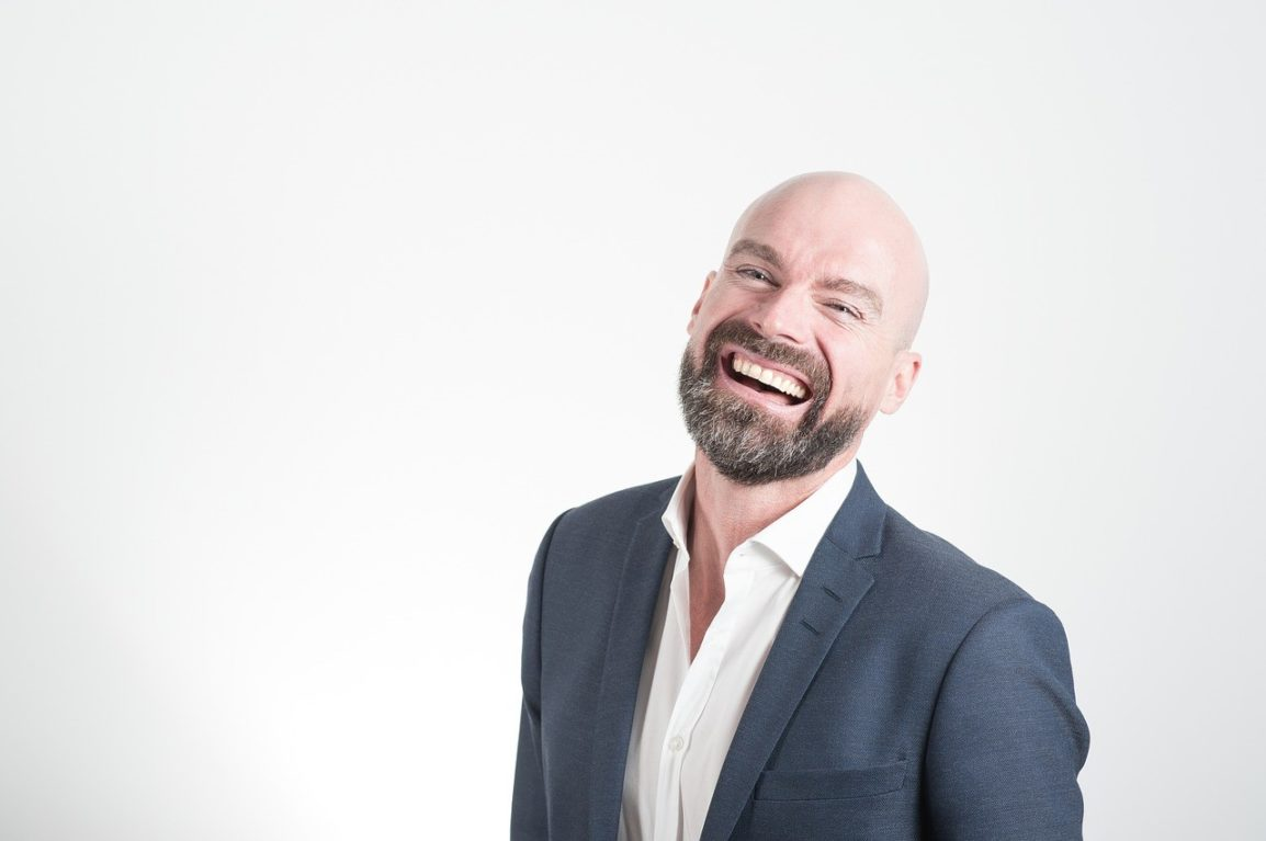 laughing bald man with a trimmed up beard and mustache wearing a suit